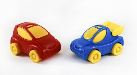 two plastic cars together, opposite each other, blue and red. On white background Banco de Imagens