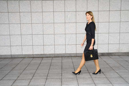 business woman with briefcase walks in front of a wall,