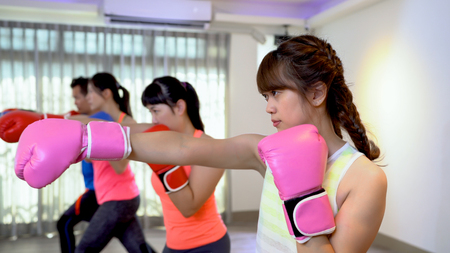 Fitness women and man training boxing workout at gym. asian people doing professional boxer poses at the class in sports club. group of sporty friends in box gloves doing exercise.