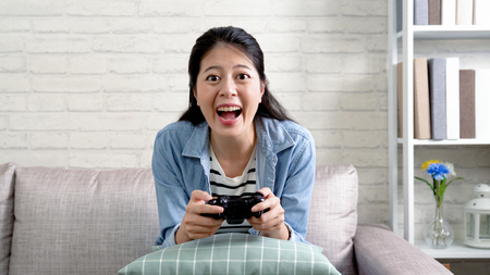 cheerful woman holding the toy controller playing video game at home. young asian girl enjoy excited having fun sitting in sofa in living room at apartment. housewife in daytime leisure lifestyle.