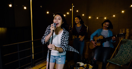 three asian love playing music on the roof. sexy singer holding microphone performing facing camera smiling singing. young ladies in the background dancing laughing.