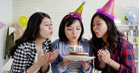 three cute ladies holding lighted cake blowing fire on candles together celebrating birthday house party. young Asians with funny hats finished making wishes. confident friends clapping hands. Stock Photo