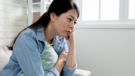 emotionele kantoordame kwam thuis van ontslagen door baas. jonge zakenvrouw verloor haar baan en voelt zich depressief terwijl ze op de bank ligt en nadenkt over de manier om met dit probleem om te gaan. vrouw bezorgd serieus zitten.