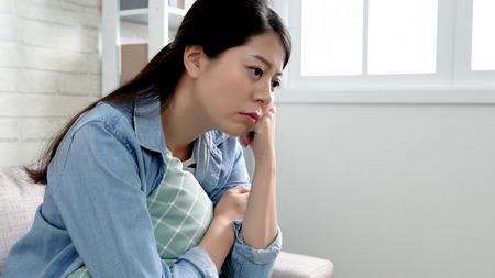 La señora de la oficina emocional llegó a casa después de haber sido despedida por su jefe. La joven empresaria perdió su trabajo y se siente deprimida descansando en el sofá y pensando en la forma de afrontar este problema. mujer preocupada seria sentarse.
