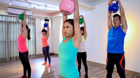 Fitness women and man exercising indoors using kettlebell in cross training. sporty models and instructors showing two-arm kettlebell swing. group of asian strong people raising dumbbells over head.