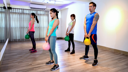 Women and man weightlifting kettlebell weight at indoor fitness gym. female and male athlete strength training legs glutes back lifting free weights. group of asian doing workout with dumbbells.
