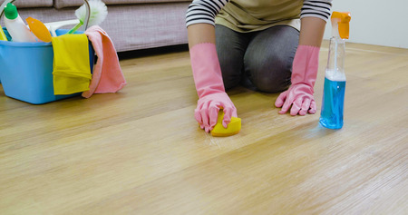 A woman hand using scouring pad wipe the wooden floor. close up photo of unrecognized female wearing protective pink gloves mopping floor doing housework. lady housewife kneeling down in living room. Imagens