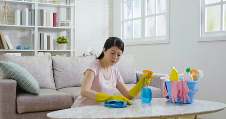 Cleanness is in trend. Pretty smiling woman wiping white marble table with blue cloth and special means of washing. young asian housekeeper wearing rubber protective gloves doing housework indoors. Archivio Fotografico