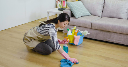 young Japanese woman wipes the floor in the cozy living room at home. lady wearing apron doing housework kneeling on wooden ground. beautiful housewife hands in rubber gloves holding rag and spray.