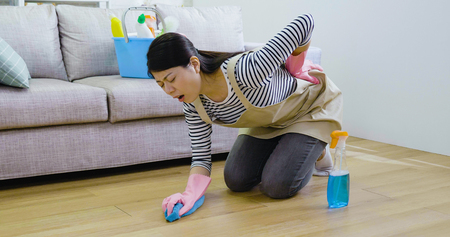 young housewife feeling waist pain back tired kneeling on the wooden floor while mopping sweeping the living room. lady wearing protective gloves and apron cleaning up house before new year.