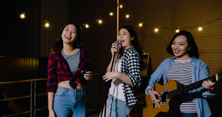 group of asian female relaxing on rooftop party at dark midnight. three girls consist a rock band playing guitar singing songs enjoying music. young ladies cheerfully chilling out on roof.