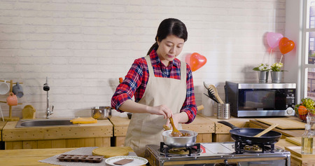 pretty asian woman wear apron standing by the stove in wooden kitchen cooking. young girl holding wood spoon stirring in pot melted chocolate in liquid. handmade gift for valentine's day concept.