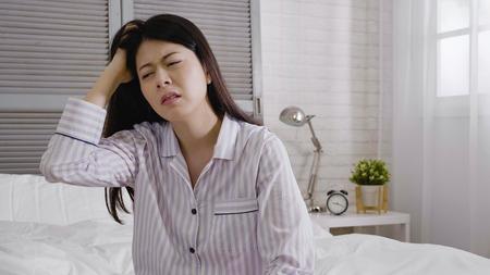Slaperige jonge aziatische vrouw die zich slaperig voelt na het wakker worden in bed. Stockfoto