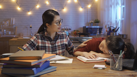 hard working concentrated asian female classmate waking her friend up to stay up late at night prepare for text exam.