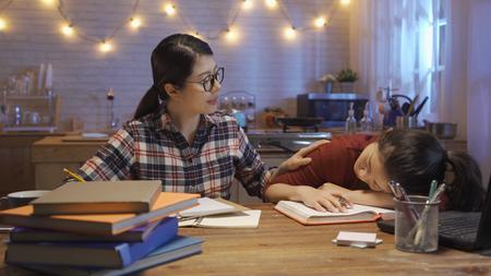 Une camarade de classe asiatique concentrée travaille dur et réveille son amie pour qu'elle veille tard dans la nuit pour se préparer à l'examen de texte.