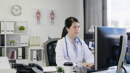 Portrait of young asian professional female doctor working at clinic office.