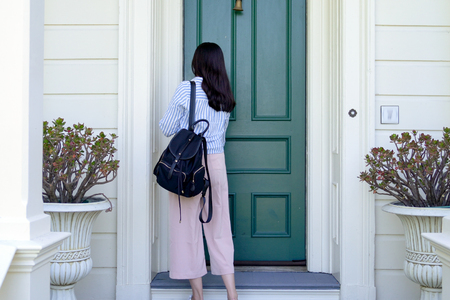 back view of girl college student carrying backpack back to home using key opening door. Stockfoto