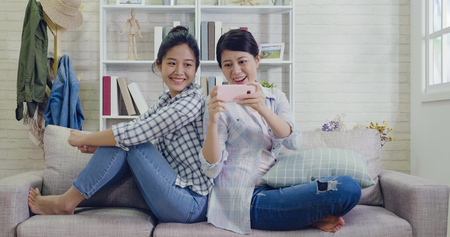friendship technology at home concept. female roommates showing smartphone sitting back to back turning around on sofa in the living room.