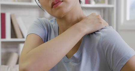 Woman with pain in shoulder and upper arm.  young asian massage neck to release painful indoors at home. Imagens