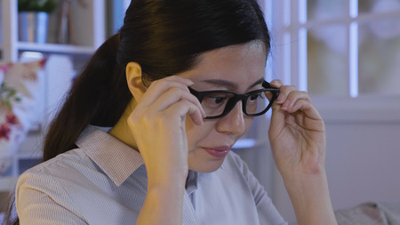 office lady feeling eye strain exhausted wearing on glasses and keep work in concentrated looking at screen  in dark living room at home in midnight. Stock Photo