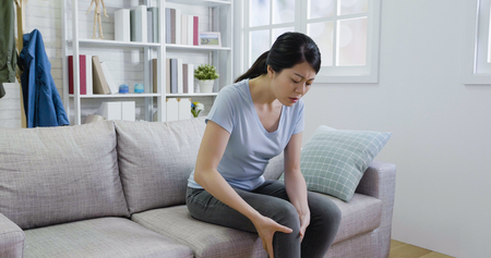 young woman suffering from leg pain with painful face. Stock Photo - 119958393
