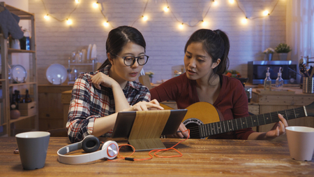 Attractive best friend woman touching digital pad discussing with sister while practicing guitar and singing. young girls use tablet for showing lyrics to roommate writing song together night kitchen