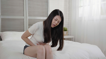 Healthcare medical daily life concept. young asian lady have stomachache or menstruation pain sitting on bed in cozy bright white bedroom. girl frowning feeling bad stomach hurt resting at home.