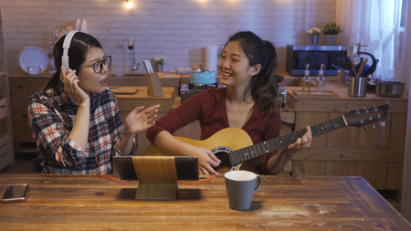 two young funny asian girls singing wearing headset and playing acoustic guitar sitting at wooden desk with warm kitchen in background. Sisters having fun leisure at home night. digital pad on table