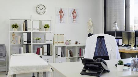 Arztbürotisch und -stuhl mit weißem Laborkittel und hellem und modernem leerem Arbeitsplatz im Krankenhaus.