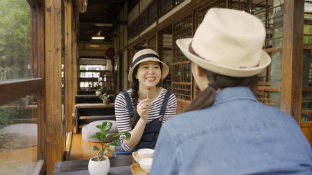 Two girls tourists drink tea and talking sitting on floor in wooden japanese house. young cheerful smiling woman with sweet on stick eating dessert laughing chatting with friend. asian female in hats