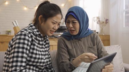 les étudiants asiatiques de plusieurs collèges étudient à l'étranger restent dans un dortoir pendant les vacances. les colocataires chinois et musulmans ont peur de regarder un film d'horreur discutant sur une tablette pointer le doigt vers l'écran assis sur un canapé.