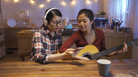 two young asian girls playing music together in house kitchen at night. woman with headphones showing friend cellphone with song app looking lyrics while roommate playing guitar. group enjoy female Stock Photo