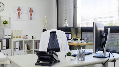 helle und moderne Arztpraxis mit PC und Telefon auf dem Schreibtisch weißer Laborkittel auf dem Stuhl. leer niemand im zimmer in der klinik. Krankenhausarbeitsplatz mit Sonnenschein durch Fenster. Standard-Bild