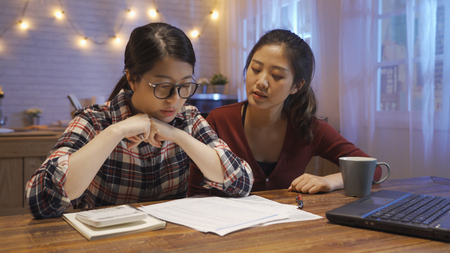 worried asian woman in glasses sitting in kitchen table looking at bills and document while accounting with calculator.