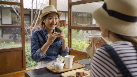 girl with surprised face holding tea drinking hot tea in japanese local wooden house sitting on floor with dessert. Imagens