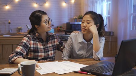 young asian woman in glasses doing accounting by laptop sitting at kitchen table at home. office lady roommate upset depressed Stock Photo
