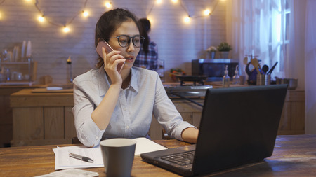 serious businesswoman talking on smart phone checking mail on netbook laptop late at night. female roommate ready to go bed standing in modern wood kitchen tidy up home waiting for friend finish work