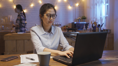 focus beautiful asian woman working on laptop computer at night in on wooden table at home. female roommate best friend holding glass of water walking in kitchen going bed. office lady type keyboard