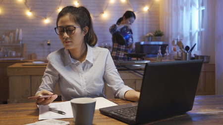 casual businesswoman using smartphone working on laptop at night. office lady look cellphone check message paperwork. rent apartment with friend thirsty roommate hold kettle drink water in kitchen Stock Photo
