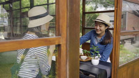 Two best friends enjoying chado ceremony in travel trip kyoto japan. young asian girls in straw hats drinking tea relaxing in japanese stye wooden house with teien. women sitting eating local sweets.