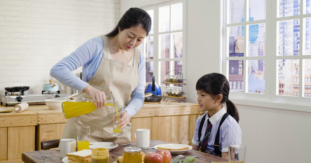 asian elegant mother in apron pouring fresh orange juice from jug for her daughter seated at wooden table in house kitchen. happy cute little girl in uniform ready for school having breakfast.
