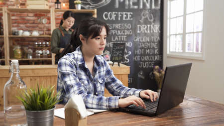Concentrated at work. Confident young asian woman in smart casual wear working on laptop computer while sitting near window in creative cafe bar. waitress in apron standing in background counter.