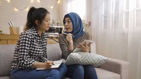 Two happy multi ethnic female students studying checking and comparing notes sitting at home kitchen in bright cozy apartment.