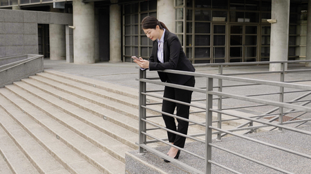 contemporary business woman leaning on handrail holding smart phone. authentic lifestyle. 免版税图像