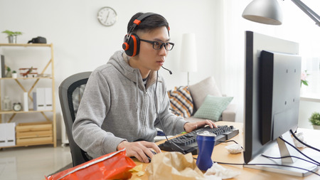copy space young asian man playing shooting video game inside messy room at home.