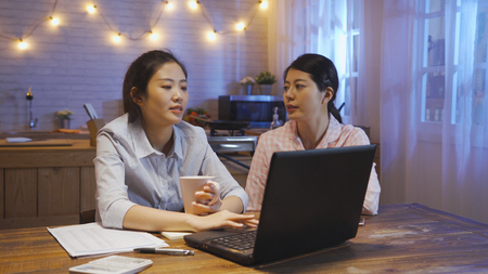 two asian women sitting at kitchen table discussing about report. female roommate in pajama care her hard working friend chatting talking before go to sleep. young office lady with cup using laptop Stock Photo