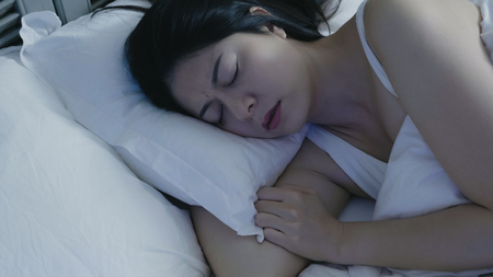 Young asian woman having nightmare in midnight. Restless dreams. female with frowning face closing eyes sleeping at night lying in white comfort bed in dark bedroom with hand under soft pillow home Фото со стока