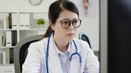 asian doctor woman feeling tired and stressed. Frustrated young medical staff keeping frowning face while sitting at working place in clinic concentrated looking at computer screen. nurse eyes pain 版權商用圖片