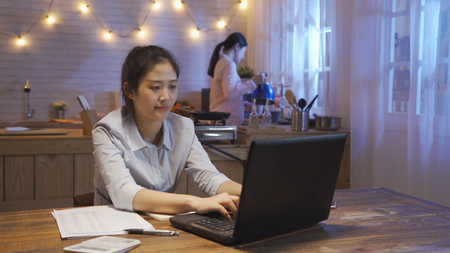 Young asian concentrated woman using laptop in the kitchen at night with female roommate in pajama hold kettle pour water thirsty going sleep. elegant office lady stay up late not resting working.