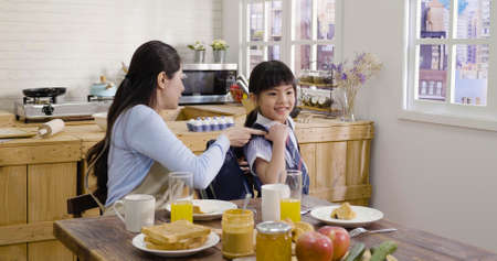 Happy smiling asian korean mother preparing backpack put bag on her kid daughter to going to kindergarten on outdoor. cute little girl with mom before the first preschool day against home breakfast Stok Fotoğraf
